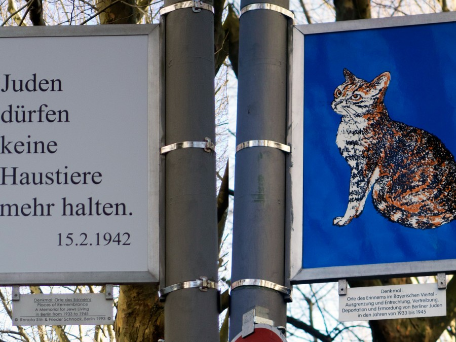 Sign post with sign of 1942 verbage in German along with image of a cat