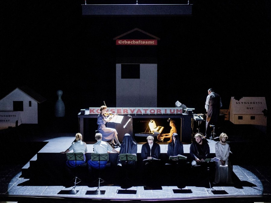 Image of konservatorium with a spotlight on a violin and piano player with 7 individuals at the foot of the stage