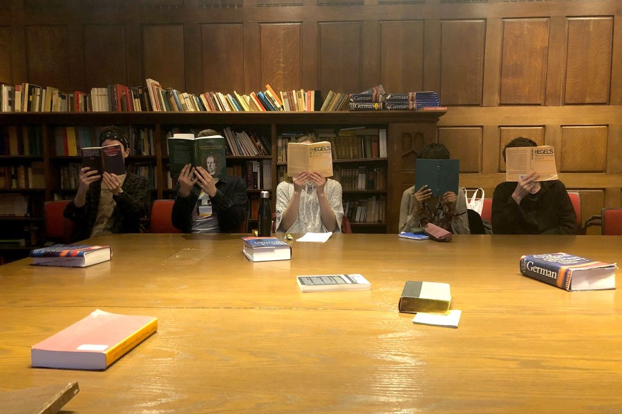 Five students in classroom with books open covering their faces