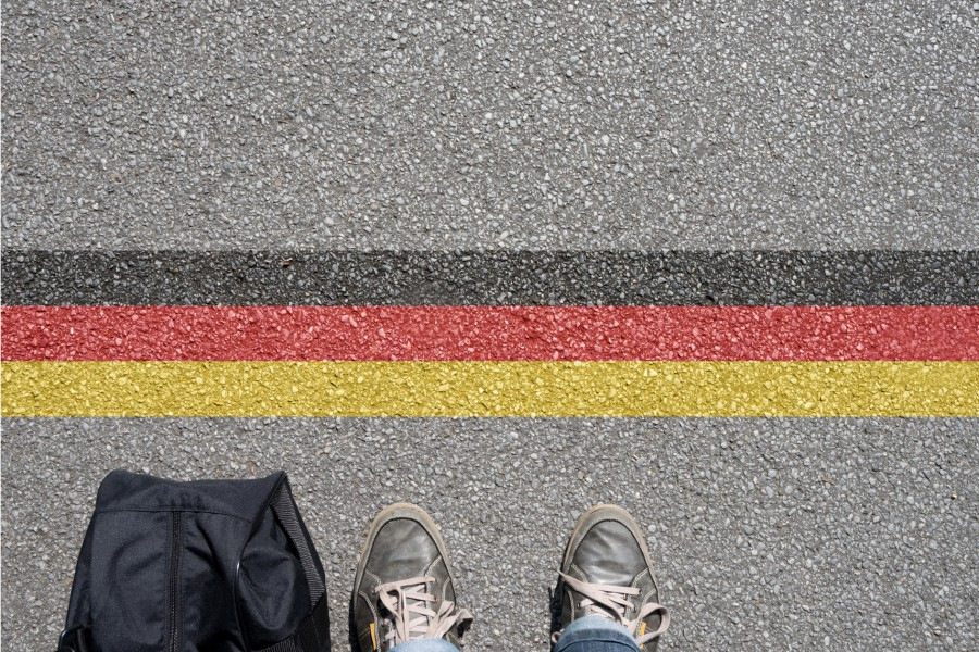Pavement view of German stripes infront of a backpack and someone's sneakers